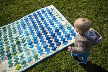 Small boy standing over his quilt