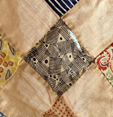 worn area of antique quilt top shows an actual hole in the fabric.