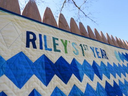 Words pieced into quilt read Riley's first year
