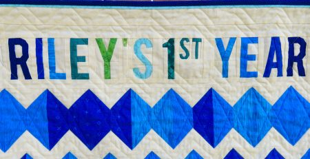 Text on quilt reads Riley's first year