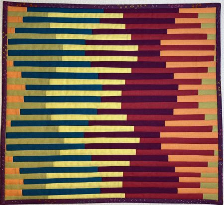 Patchwork quilt with interwoven striped effect.