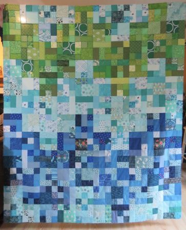 Patchwork quilt made of squares and rectangles in blues and greens.