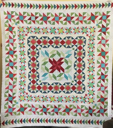 Patchwork medallion-style quilt in blues, greens and reds on a cream background.